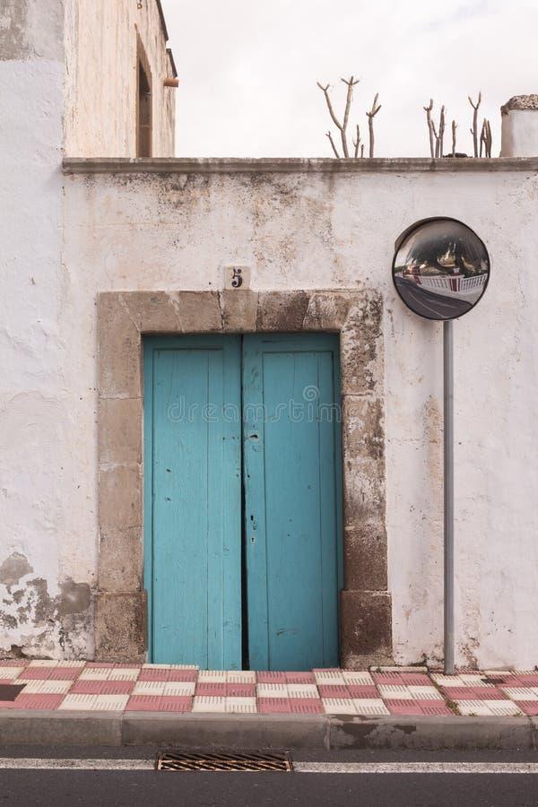 Οδός και ένα σπίτι με την μπλε ξύλινη πόρτα στοκ εικόνα