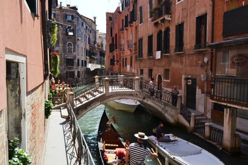 Οδός καναλιών της Βενετίας με τις γόνδολες και τους επιβάτες που κινούνται κάτω από τη γέφυρα στοκ φωτογραφία με δικαίωμα ελεύθερης χρήσης