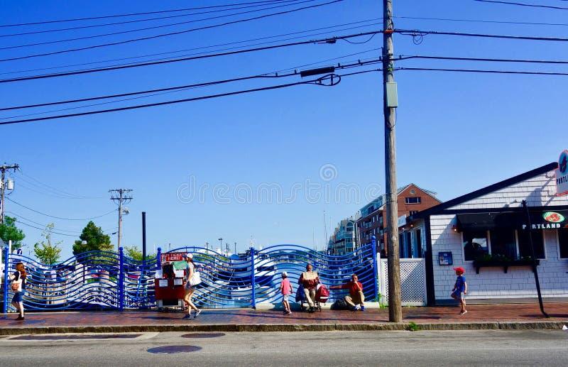 Οδός πόλεων στην κωμόπολη τουριστών με τον ασυνήθιστο κυματιστό φράκτη και το περπάτημα ανθρώπων στοκ φωτογραφία