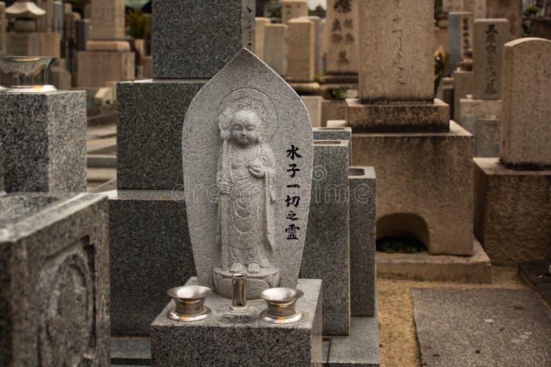ΟΖΑΚΑ, ΙΑΠΩΝΙΑ - 29 ΙΑΝΟΥΑΡΊΟΥ 2018: Γλυπτό και τάφοι πετρών του Βούδα στο cementery της Οζάκα στοκ φωτογραφία