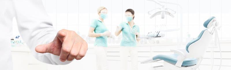 Οθόνη αφής χεριών οδοντιάτρων στην οδοντική κλινική με την καρέκλα οδοντιάτρων ` s ελεύθερη απεικόνιση δικαιώματος