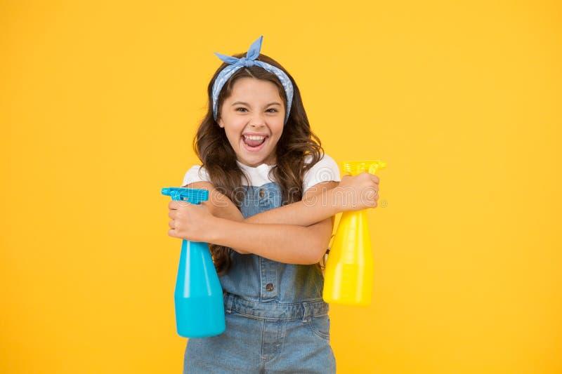Οικιακός καθαρισμός για εσάς Χαρούμενη οικιακή βοηθός σε κίτρινο φόντο Χαριτωμένο κοριτσάκι κρατά μπουκάλια σπρέι για οικιακή χρή στοκ φωτογραφία