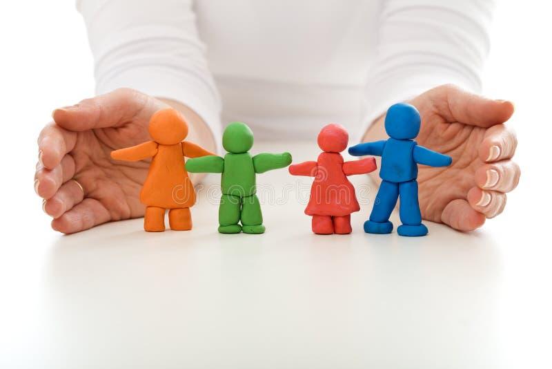 Οικογένεια ανθρώπων αργίλου που προστατεύεται από τα χέρια γυναικών στοκ εικόνα με δικαίωμα ελεύθερης χρήσης