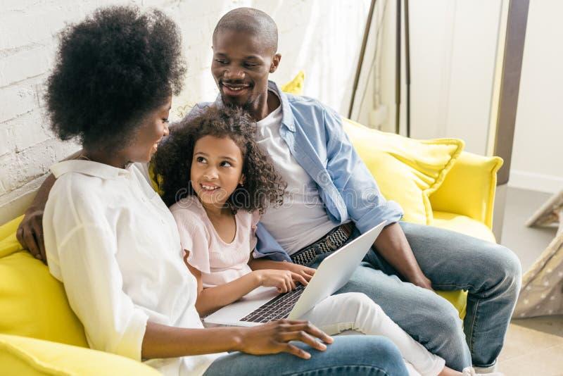 οικογένεια αφροαμερικάνων με το lap-top που στηρίζεται στον καναπέ από κοινού στοκ φωτογραφία