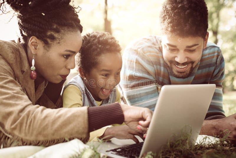 Οικογένεια αφροαμερικάνων που ξαπλώνει στο πάρκο και που χρησιμοποιεί το λ στοκ φωτογραφίες