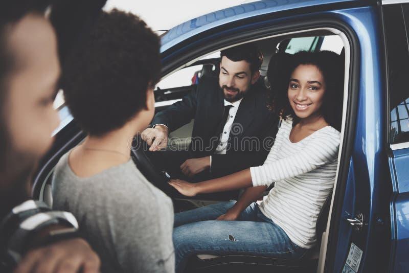 Οικογένεια αφροαμερικάνων στη εμπορία αυτοκινήτων Ο πωλητής παρουσιάζει νέο αυτοκίνητο στοκ φωτογραφία με δικαίωμα ελεύθερης χρήσης