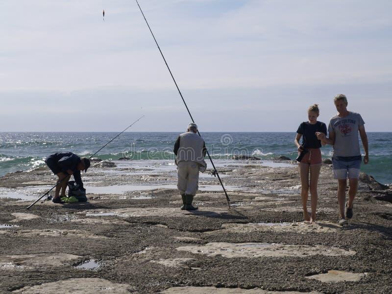 Οικογένεια δίπλα στον ψαρά στην παραλία στοκ φωτογραφία με δικαίωμα ελεύθερης χρήσης