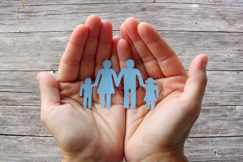 Οικογένεια εγγράφου στα χέρια στην ξύλινη έννοια ευημερίας υποβάθρου στοκ εικόνα