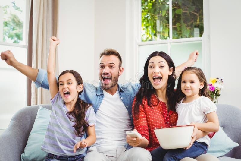 Οικογένεια ενθαρρυντική προσέχοντας τη TV στο σπίτι στοκ φωτογραφίες