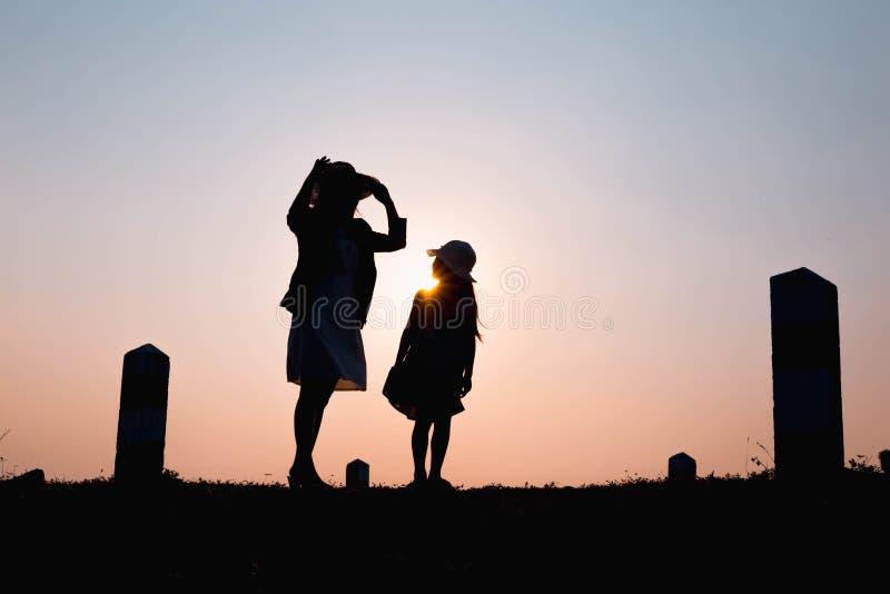 οικογένεια ευτυχής Ένα παιχνίδι μητέρων και γιων στους τομείς χλόης υπαίθρια στη σκιαγραφία βραδιού Εκλεκτής ποιότητας διάστημα τ στοκ φωτογραφία