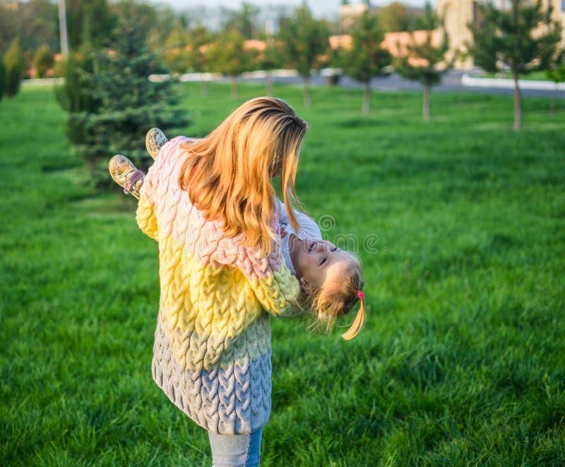 οικογένεια ευτυχής Παιχνίδι μητέρων με την κόρη της στον πράσινο χορτοτάπητα με τη χλόη στοκ φωτογραφίες με δικαίωμα ελεύθερης χρήσης