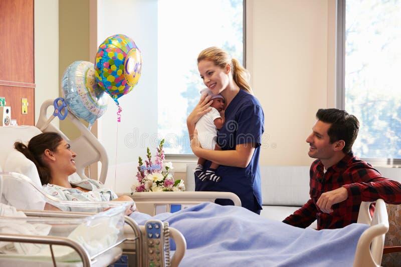 Οικογένεια και νοσοκόμα με νέο - γεννημένο μωρό στο μετα γενέθλιο τμήμα στοκ φωτογραφία