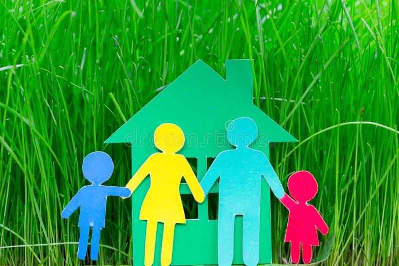 Οικογένεια και σπίτι εγγράφου στη χλόη στοκ εικόνες
