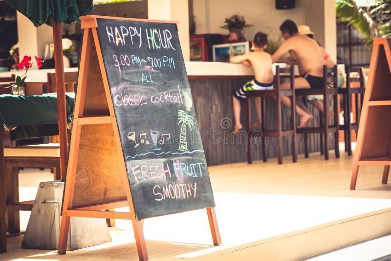 Οικογένεια κατά τη διάρκεια των ευτυχών ωρών στον τροπικό καφέ παραλιών με την πινακίδα κατά τη διάρκεια θερινή των παραθαλάσσιων στοκ φωτογραφία