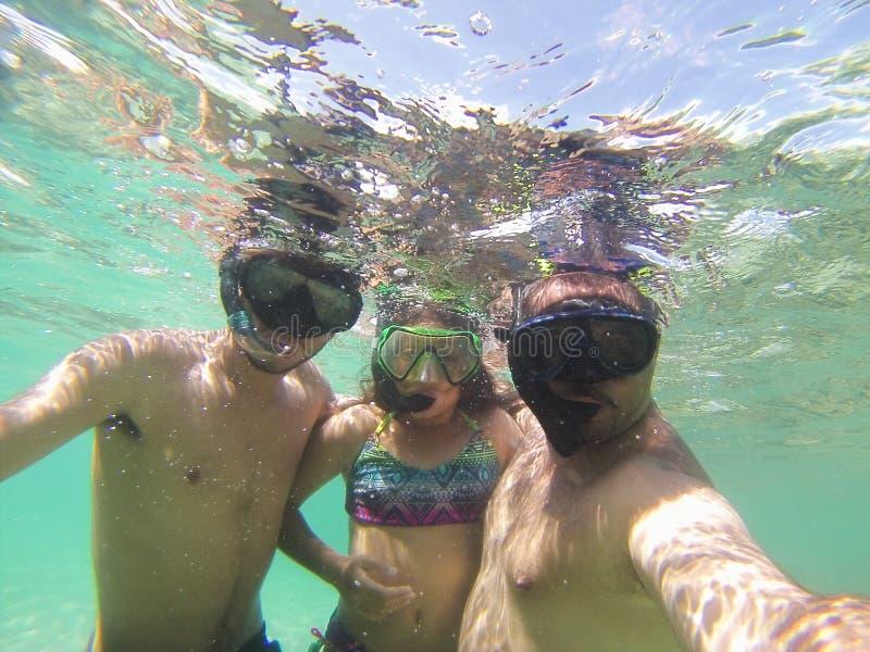 Οικογένεια κολύμβησης με αναπνευστήρα στοκ εικόνες