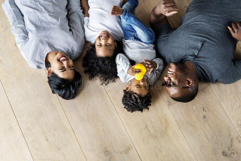 Οικογένεια μαύρων που βρίσκεται στο ξύλινο διάστημα σχεδίου πατωμάτων στοκ εικόνες