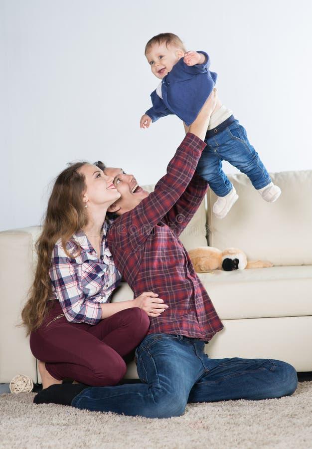 Οικογένεια με ένα μωρό σε ένα δωμάτιο με έναν καναπέ στοκ εικόνες