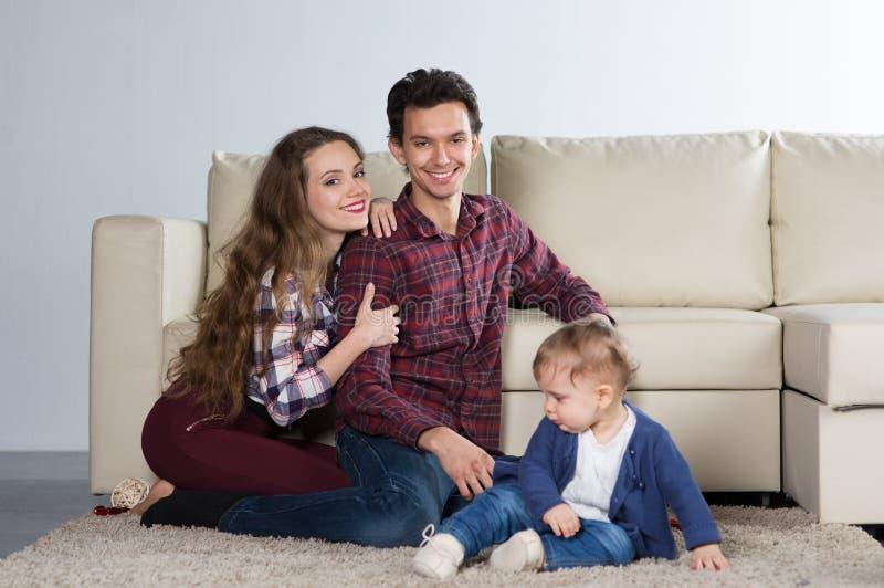 Οικογένεια με ένα μωρό σε ένα δωμάτιο με έναν καναπέ στοκ φωτογραφίες