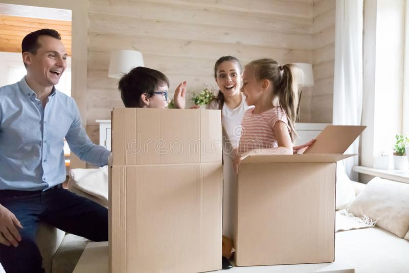 Οικογένεια με συγκινημένα τα παιδιά κινούμενα ανοίγοντας κιβώτια παι στοκ φωτογραφία με δικαίωμα ελεύθερης χρήσης