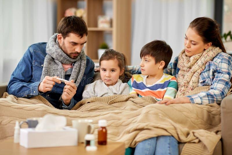 Οικογένεια με τα άρρωστα παιδιά που έχουν τον πυρετό στο σπίτι στοκ εικόνες
