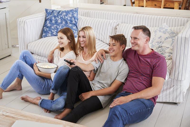Οικογένεια με τα εφηβικά παιδιά που κάθονται στον καναπέ που προσέχει τη TV από κοινού στοκ εικόνα με δικαίωμα ελεύθερης χρήσης