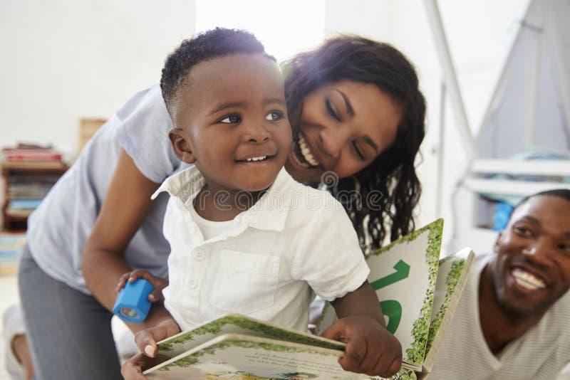 Οικογένεια με τα μικρά παιδιά που διαβάζουν το βιβλίο στο χώρο για παιχνίδη από κοινού στοκ φωτογραφία