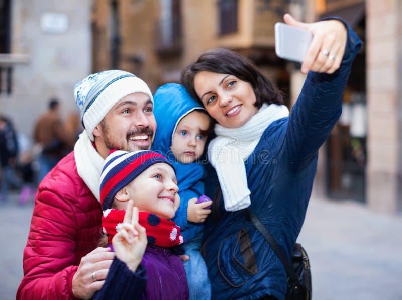 Οικογένεια με τα παιδιά που περπατούν την πόλη και που κάνουν selfie στοκ εικόνα με δικαίωμα ελεύθερης χρήσης