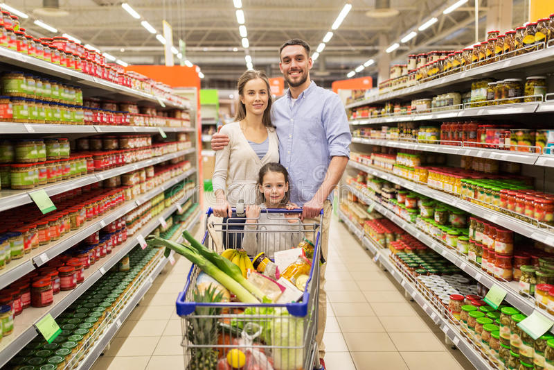 Οικογένεια με τα τρόφιμα στο κάρρο αγορών στο μανάβικο στοκ εικόνες