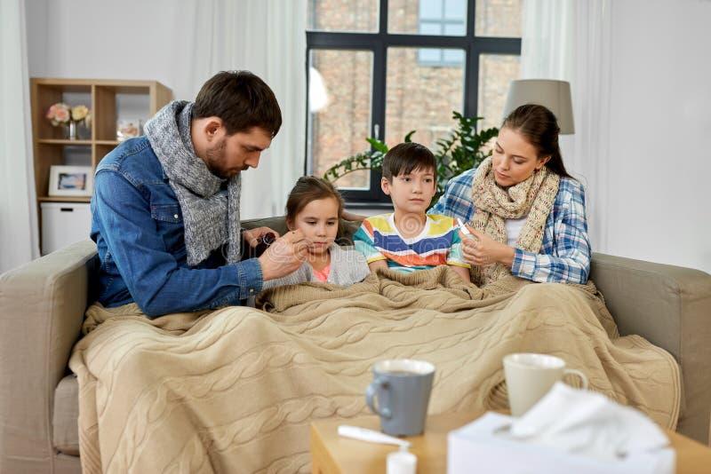 Οικογένεια με την ιατρική που θεραπεύει τα άρρωστα παιδιά στο σπίτι στοκ φωτογραφία