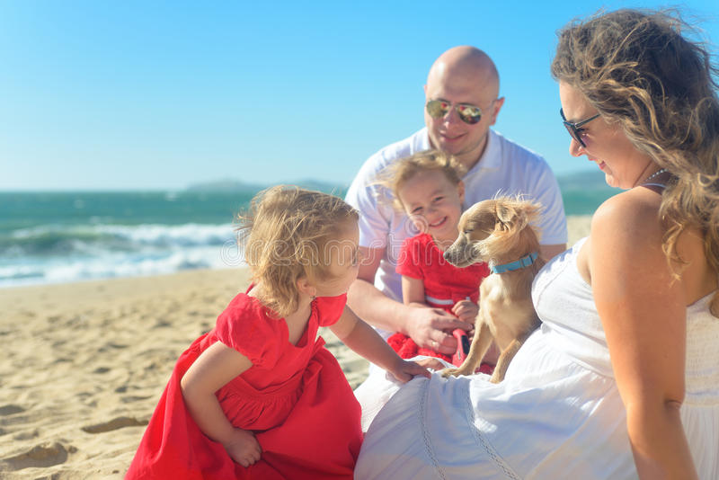 Οικογένεια με τις αδελφές στο κόκκινα φόρεμα και το σκυλί στην παραλία στοκ φωτογραφίες με δικαίωμα ελεύθερης χρήσης