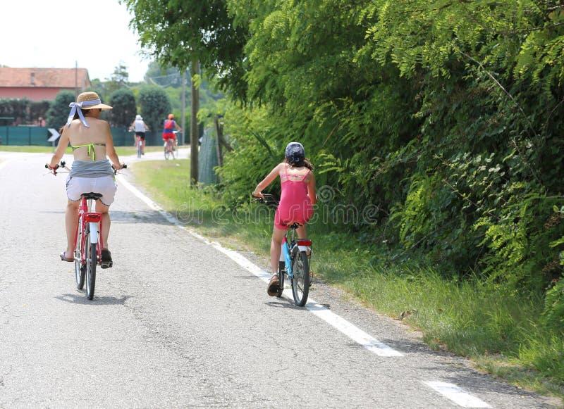 Οικογένεια με το mom και νέο πεντάλι κορών στο στρωμένο δρόμο στοκ φωτογραφία με δικαίωμα ελεύθερης χρήσης