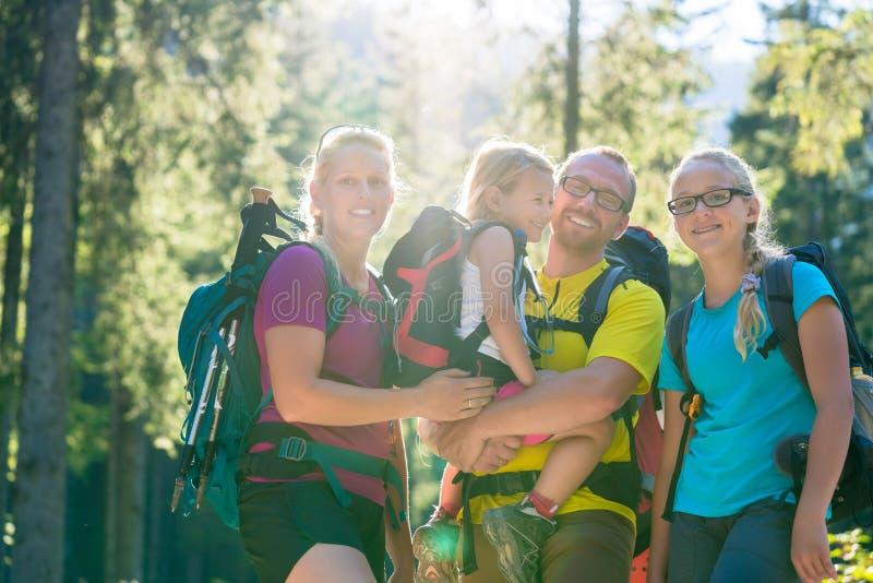 Οικογένεια με δύο κόρες στο πεζοπορώ στα ξύλα στοκ φωτογραφία με δικαίωμα ελεύθερης χρήσης