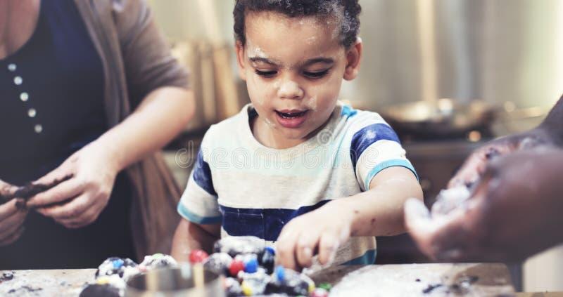 Οικογένεια μικρών παιδιών που ψήνει τη σπιτική έννοια μπισκότων στοκ φωτογραφίες