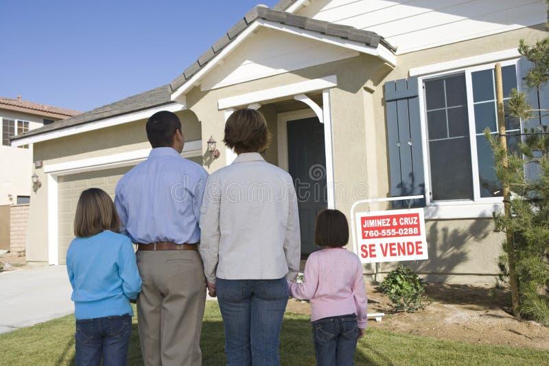 Οικογένεια μπροστά από το σπίτι για την πώληση στοκ εικόνες με δικαίωμα ελεύθερης χρήσης