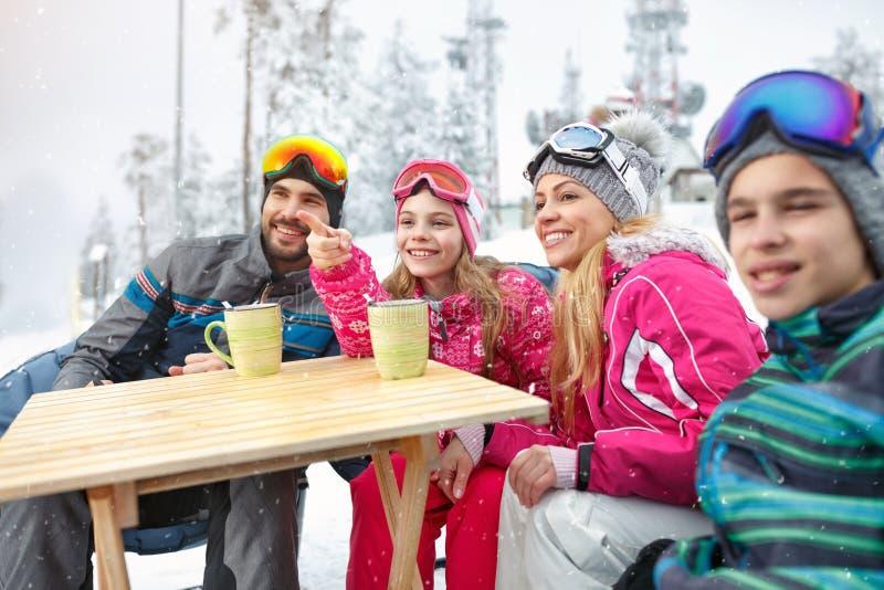 Οικογένεια να κάνει σκι που φαίνεται κάτι στην απόσταση στοκ φωτογραφίες