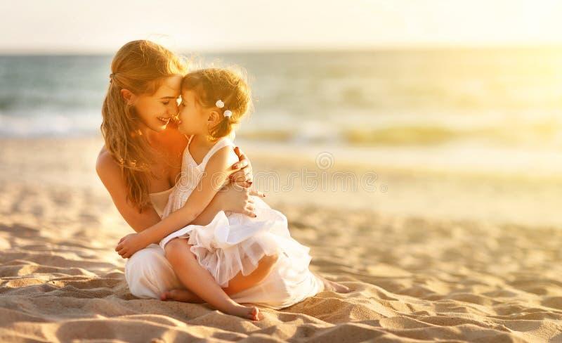 οικογένεια παραλιών ευ&ta μητέρα που αγκαλιάζει την κόρη μωρών στο ηλιοβασίλεμα στοκ εικόνες