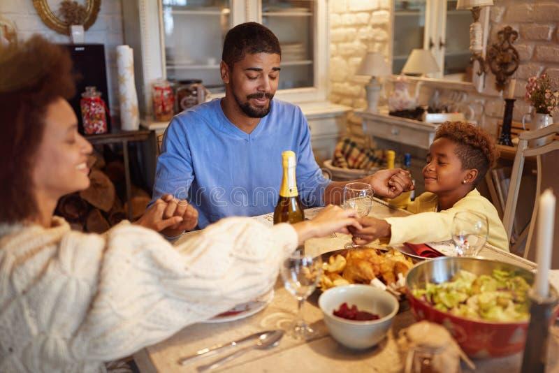 Οικογένεια που έχει την προσευχή Χριστουγέννων για το γεύμα στο σπίτι στοκ φωτογραφία με δικαίωμα ελεύθερης χρήσης