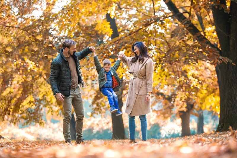 Οικογένεια που έχει τη διασκέδαση στο πάρκο φθινοπώρου με το γιο του στοκ φωτογραφίες με δικαίωμα ελεύθερης χρήσης