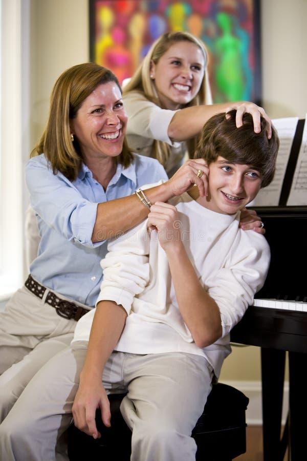 Οικογένεια που έχει τον πειράζοντας έφηβο διασκέδασης στο σπίτι στοκ εικόνες με δικαίωμα ελεύθερης χρήσης