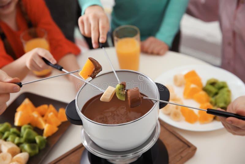 Οικογένεια που έχει fondue το γεύμα στον πίνακα στοκ εικόνες