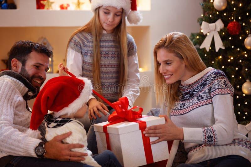Οικογένεια που απολαμβάνει μοιραμένος τα χριστουγεννιάτικα δώρα στο σπίτι στοκ εικόνα