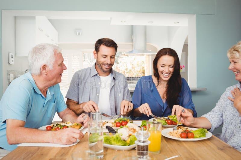 Οικογένεια που γελά καθμένος να δειπνήσει στον πίνακα στοκ φωτογραφίες