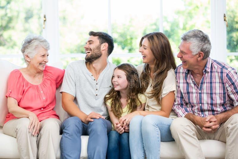 Οικογένεια που γελά καθμένος στον καναπέ στοκ φωτογραφία με δικαίωμα ελεύθερης χρήσης