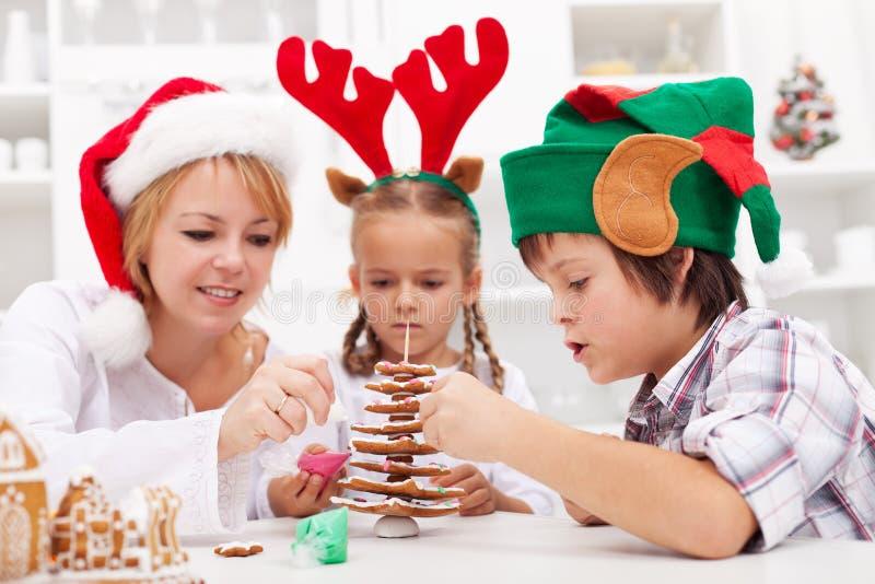 Οικογένεια που διακοσμεί το χριστουγεννιάτικο δέντρο μελοψωμάτων στοκ εικόνες με δικαίωμα ελεύθερης χρήσης