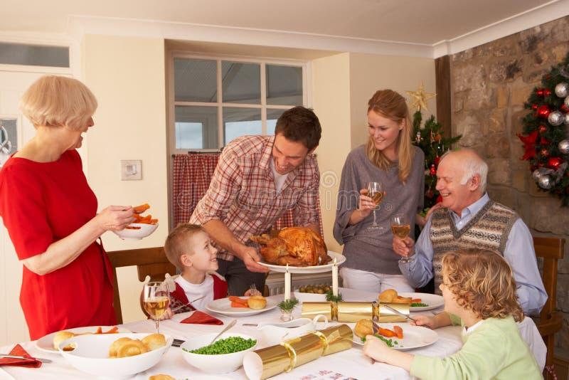 Οικογένεια που εξυπηρετεί στο σπίτι το γεύμα στα Χριστούγεννα στοκ φωτογραφίες
