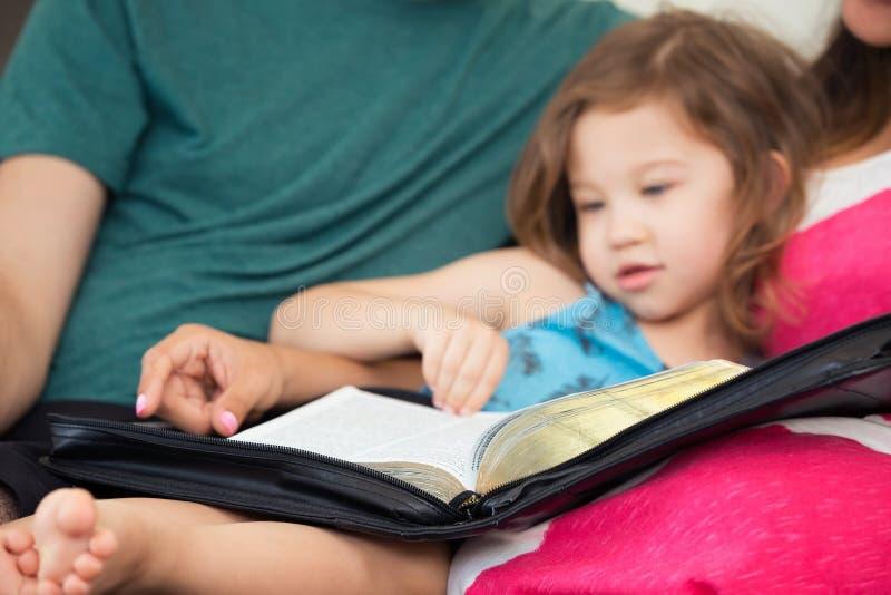 Οικογένεια που διαβάζει τη Βίβλο από κοινού στοκ φωτογραφίες με δικαίωμα ελεύθερης χρήσης