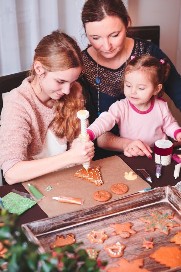 Οικογένεια που διακοσμεί τα μπισκότα μελοψωμάτων Χριστουγέννων στοκ φωτογραφία με δικαίωμα ελεύθερης χρήσης