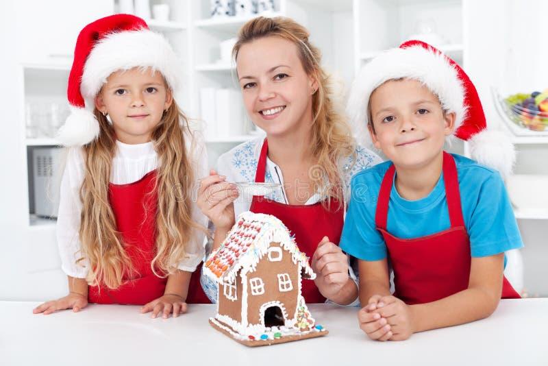 Οικογένεια που κάνει ένα σπίτι μπισκότων μελοψωμάτων στοκ φωτογραφία