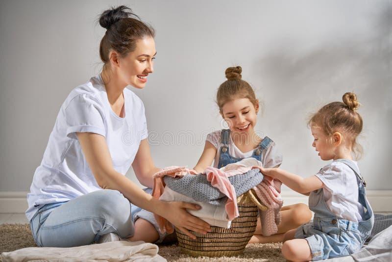 Οικογένεια που κάνει το πλυντήριο στο σπίτι στοκ εικόνα με δικαίωμα ελεύθερης χρήσης