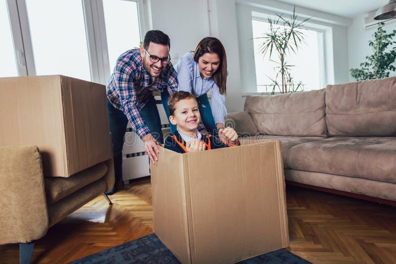 Οικογένεια που κινείται κατ' οίκον με τα κιβώτια γύρω, και που έχει τη διασκέδαση στοκ φωτογραφία